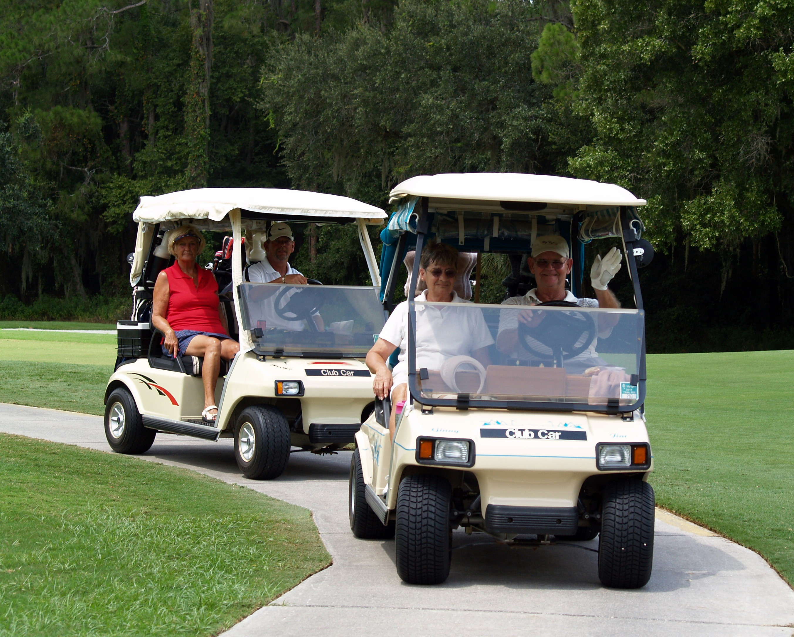 Two smiling couples in golf carts