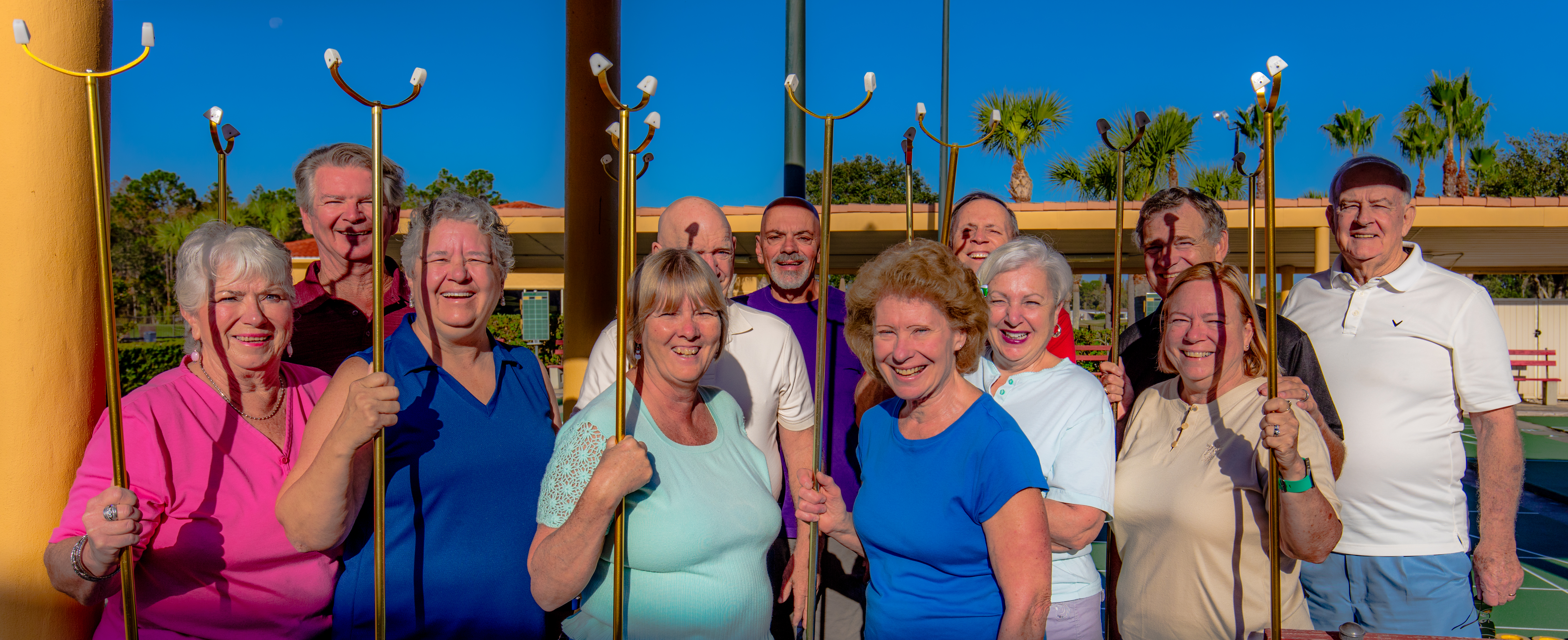 Group of 12 smiling senior men and women in casual dress holding shuffleboard sticks in front of shuffleboard court