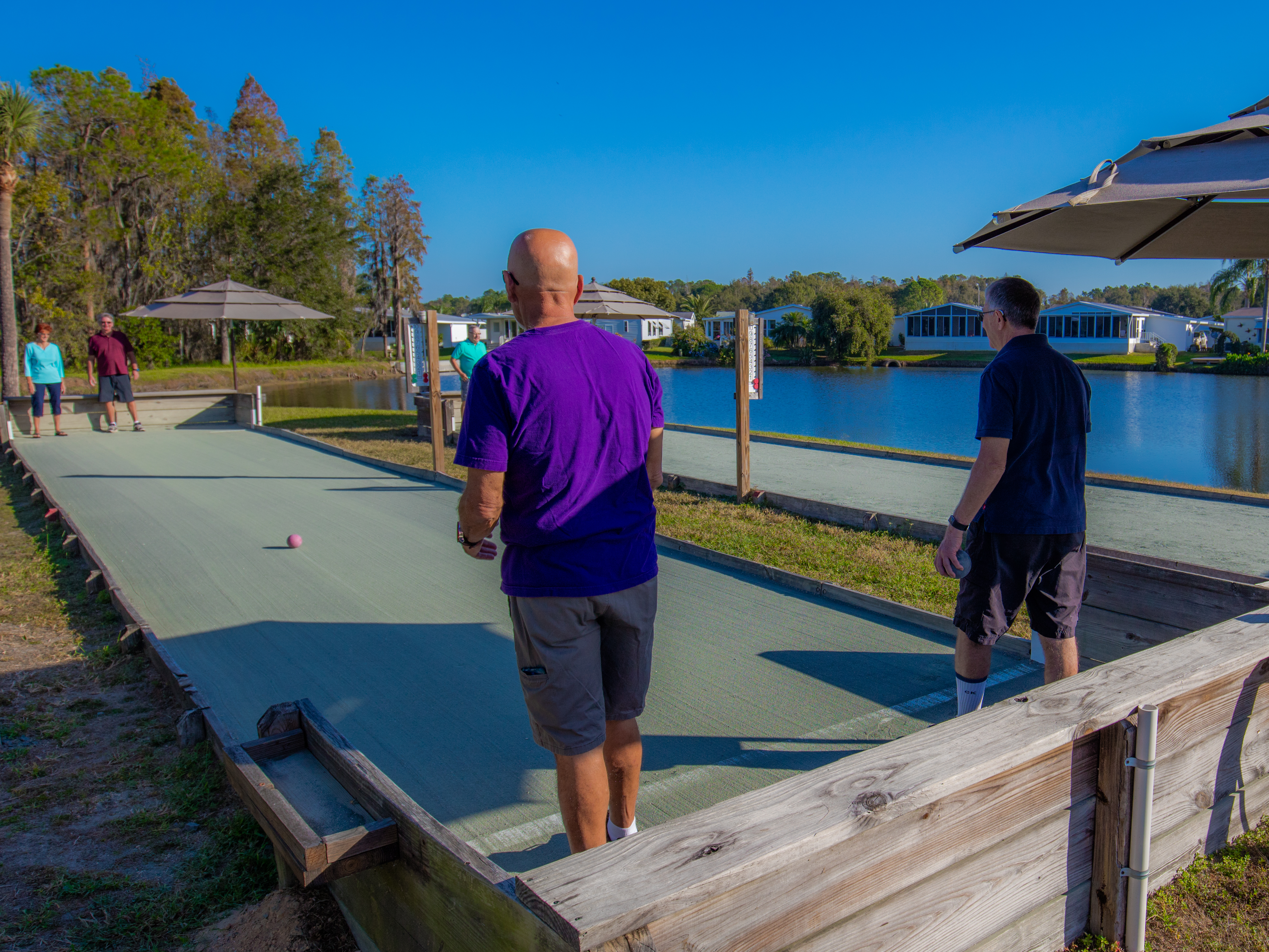 Two older men with backs to camera watch as their bocce balls roll down the court to a couple on the other end; there's a lake surrounded by manufactured homes in the background.
